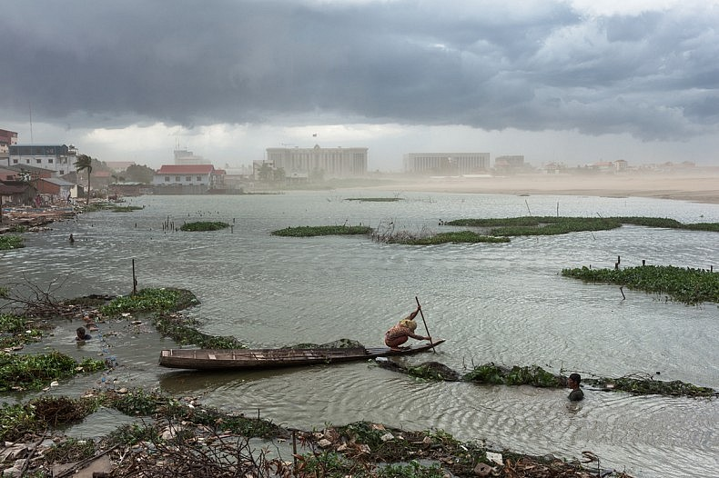 July 07, 2011 - Phnom Penh, Cambodia. A resident of Boeung Kak rows a wooden boat against a storm moving in over Phnom Penh. The new buildings of the Council of Ministers and the office of the Prime Minister can be seen in the background. © Nicolas Axelrod / Ruom