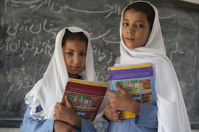 Haseena, nine years old, left, and Nadia, twelve years old.  The sisters are the second generation of Afghan refugee girls to attend Asifi's school. Their mother, Salma, was among the first girl students two decades ago.
