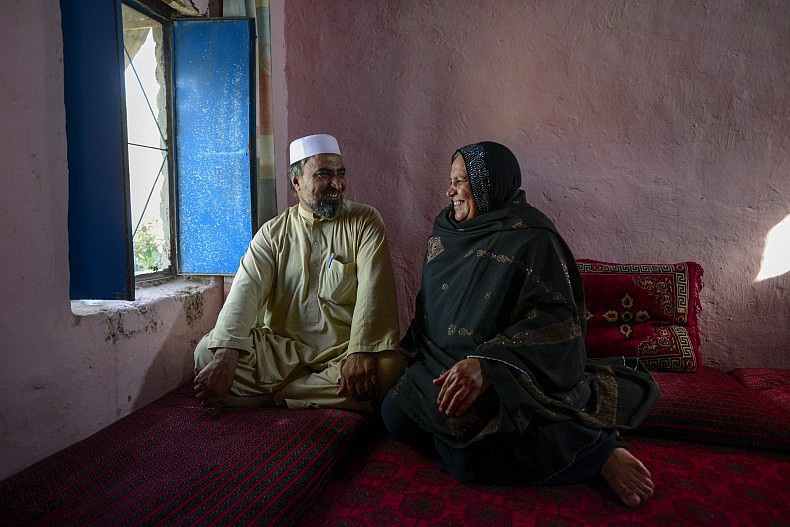 """Asifi with her husband Sher Muhammad in their home. He has championed her work with refugee girls from the beginning: """"In the future I would like [the schools] to go beyond 8th grade and include technical schools, so they can play a positive role in the development of Afghanistan,"""" says Muhammad. UNHCR/S. Rich"""