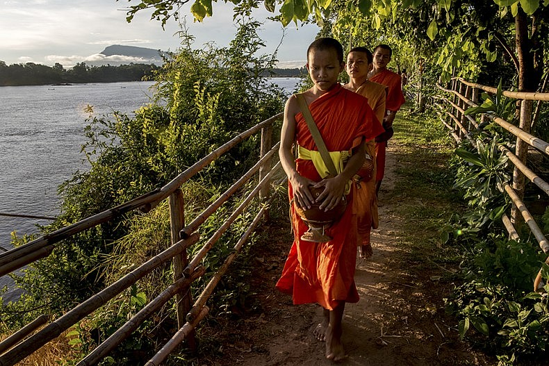 Young Novice Monks beg for alms in the early morning light on a small