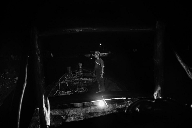 A crew member prepares the shrimp boat to head into the South China Sea, known as the Eastern Sea in Vietnam. Photo by Gareth Bright.