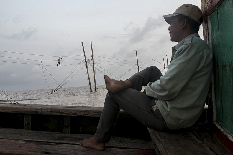 Captain Nguyen Than sits on his shrimp boat, 30 km off the coast of Vietnam. In the background, a man traverses a line strung between the offshore nets. The nets are manned by a remote crew that lives in stilted shacks 30 km away from land. Every 8 or 9 days the crew members will rotate, and the men living offshore return to land. Photo by Luc Forsyth.