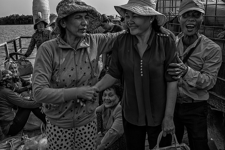 Passengers delight in having their photograph taken on board the ferry from mainland Den Do to the small island of Phu Thanh in southern Vietnam. Ferries are used as transport throughout the Mekong Delta Region, a maze of small canals, rivers and arroyos interspersed with villages and floating markets. Photo by Gareth Bright.