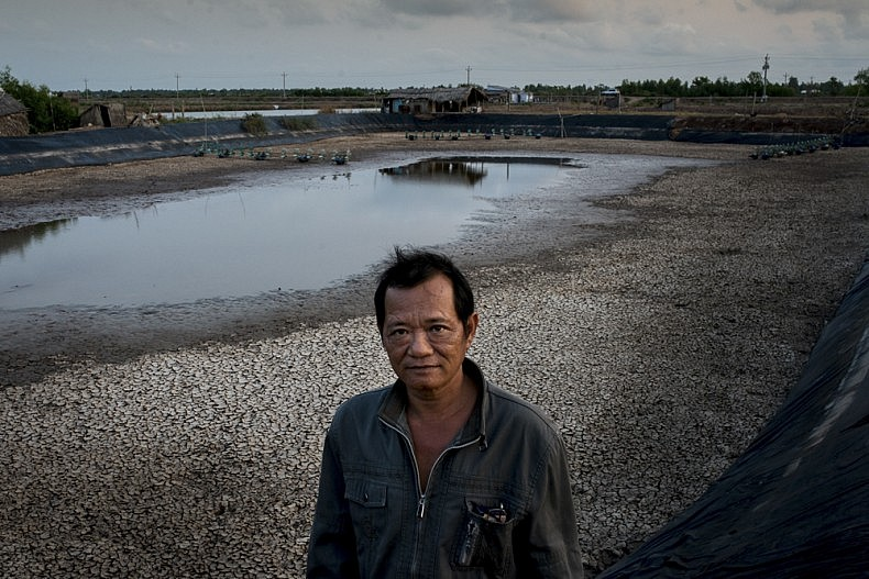 Shrimp farmer Tan Van Vu stands in front one of his drained ponds. Photo by Luc Forsyth.