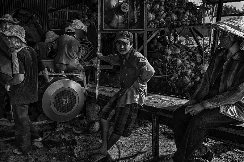 Workers feed coconut husks into a grinding machine. Photo by Gareth Bright.