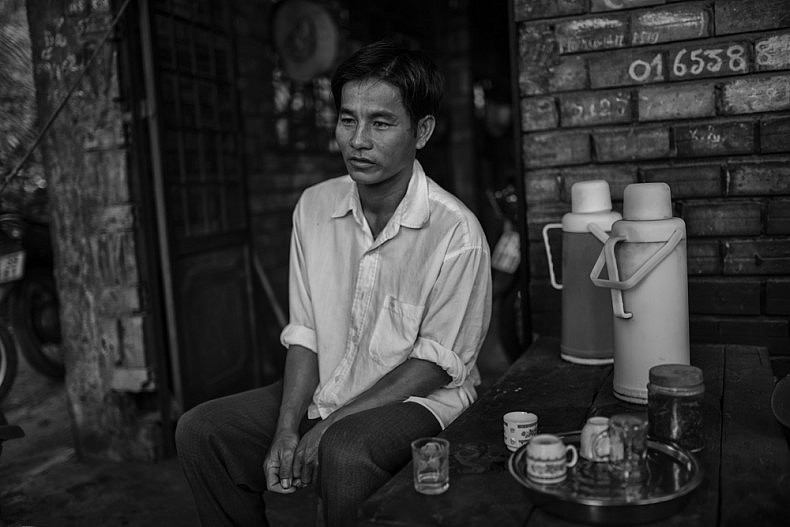 Shipyard manager Muoi drinks tea before the day's work begins.  Photo by Gareth Bright.