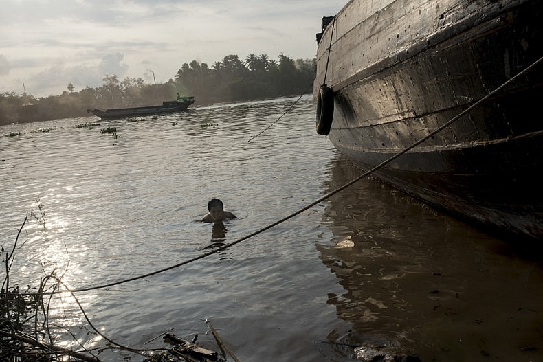 A worker submerges himself in the Mekong before a team attempts to salvage a piece of sunken lumber. Photo by Luc Forsyth.