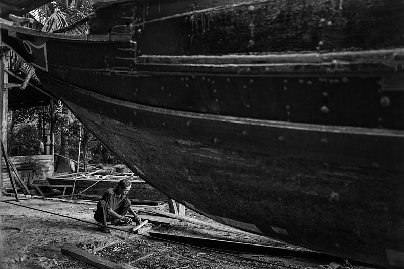 A shipyard worker rims pieces of wood in the shadow of a boat under repair. Photo by Gareth Bright.