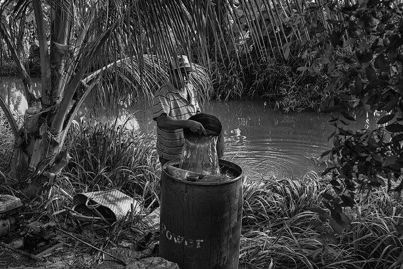 A man collects water from one of the irrigation canals that run between the fields. Photo by Gareth Bright.