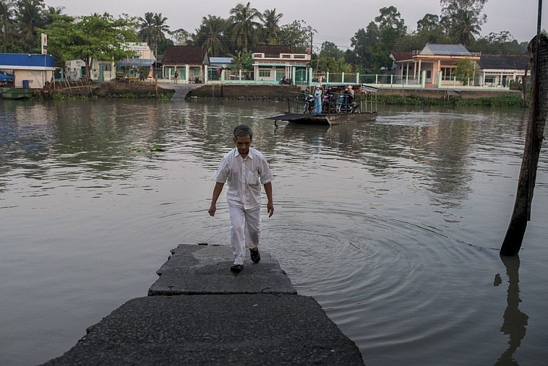 Dan, a follower of the Cao Dai religion, walks up a ferry jetty on his way to visit his ailing sister on the outskirts of Can Tho. Photo by Luc Forsyth.