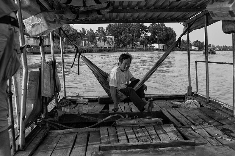 A ferry driver sits in his make shift hammock as he navigates one of the many canals that divide and connect the Mekong Delta. Ferries are used as transport throughout the Mekong Delta Region, a maze of small canals, rivers and arroyos interspersed with villages and floating markets. Photo by Gareth Bright.