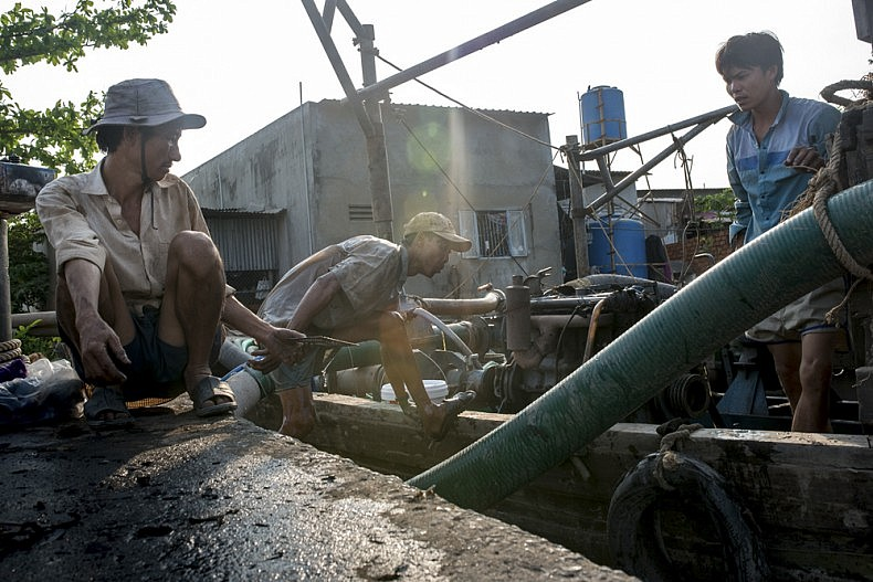 Workers clean parts of an engine in the river in the city of Can Tho. Photo by Luc Forsyth.
