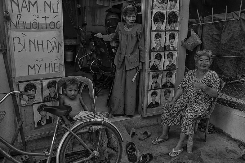 A family in front of their home and family-run salon in the neighborhood of Fisherman's Village in the city of Can Tho. Photo by Gareth Bright.