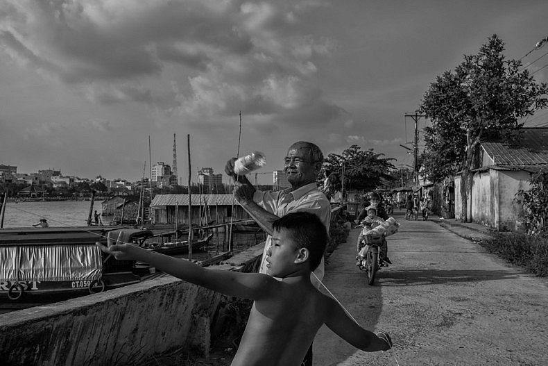 Residents of Fisherman's Village fly kites in the afternoon in the city of Can Tho. Photo by Gareth Bright.