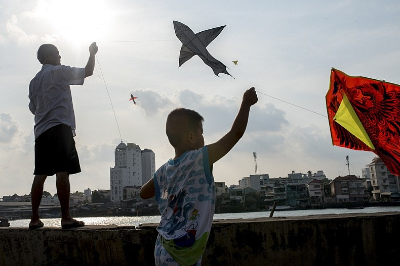 Residents of Fisherman's Village fly kites in the afternoon in the city of Can Tho. Photo by Luc Forsyth.