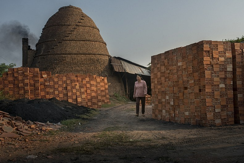 The brick factory owner walks her property in the early morning. Photo by Luc Forsyth.