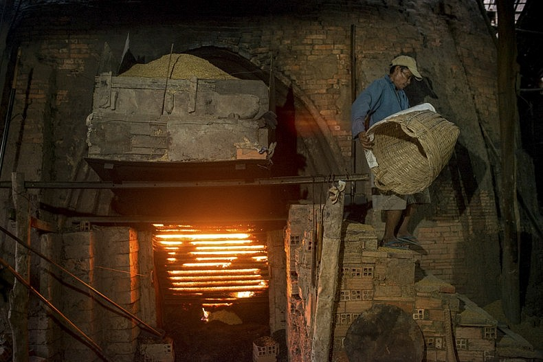 A worker carries a load of rice husks to a hopper which feeds into one of the factory's brick kilns. Photo by Luc Forsyth,