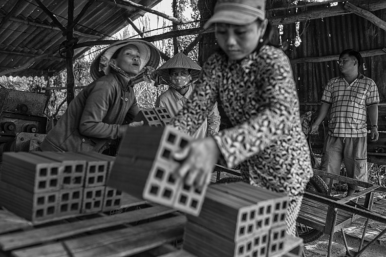 Workers move freshly cut bricks onto a cart before moving them into the sun to dry.  Photo by Gareth Bright.