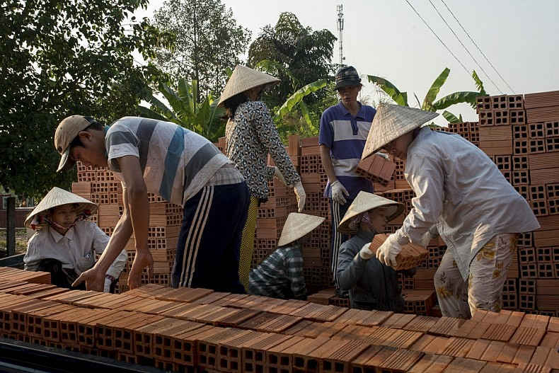 Workers load finished bricks onto waiting trucks so they can be transported to local construction sites. Photo by Luc Forsyth.