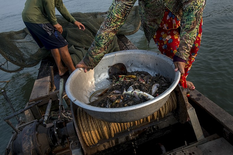 Plastic is mixed in with each net of fish. In some cases, the amount of plastic debris outnumber the fish. Throughout Vietnam's Mekong delta, locals report drastic decreases in the numbers of fish being caught in the river. Photo by Luc Forsyth.
