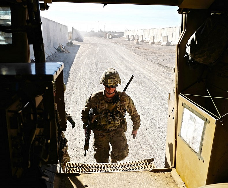 A soldier of the U.S. infantry platoon providing security for the NATO advisors entering a Mine-Resistant Ambush Protected (MRAP) vehicle. Photo by Franz-Stefan Gady.