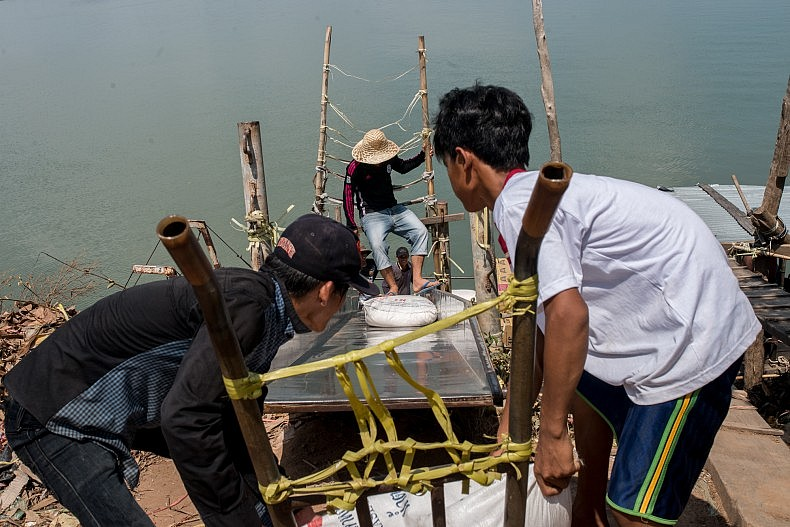 Men load cargo on the Cambodian side of the border. Photo by Luc Forsyth.