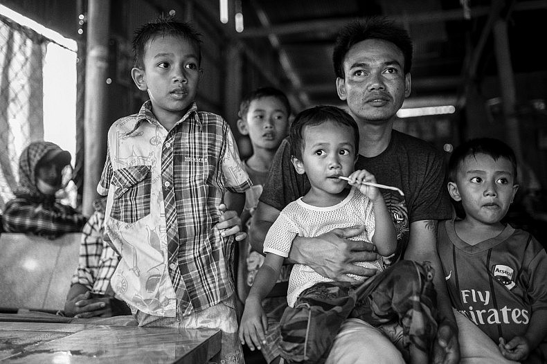 A local family sits in a cafe while explaining their plight to survive in the face of heavy erosion in the village of Khpob Ateav. The Mekong's banks are eroding at the rate of roughly 4-5 metres per year in the area, and the brothers will have to dismantle their home and move within months or else it will collapse into the water below. Photo by Gareth Bright.