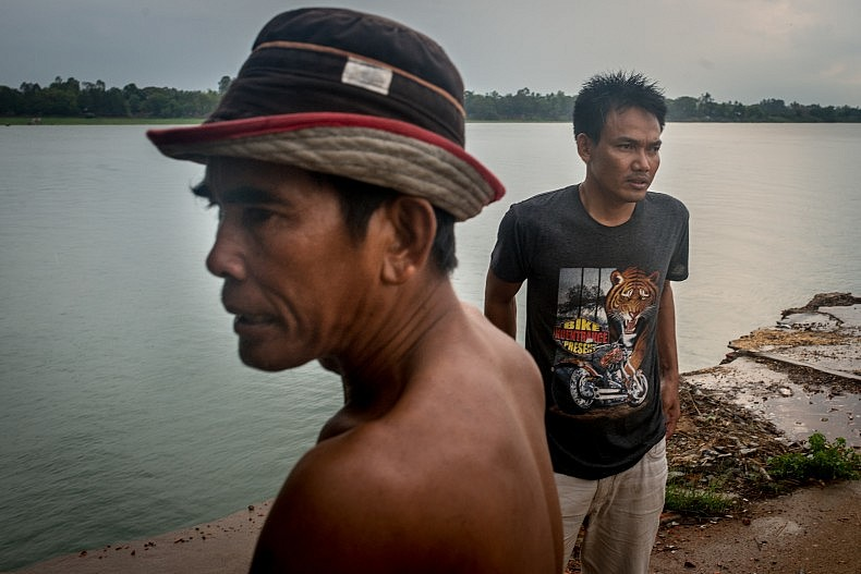Yea Buthea, 50, (foreground) and his brother Yen Bunsong, 35, (background), stand on the edge of their family property. The Mekong's banks are eroding at the rate of roughly 4-5 meters per year in the area, and the brothers will have to dismantle their home and move within months or else it will collapse into the water below. Photo by Luc Forsyth.