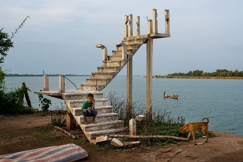 A boys sits on a staircase on the edge of the Mekong. The stairs are the only remains of a house whose owners were forced to relocate as river erosion washed away their land. Photo by Luc Forsyth.