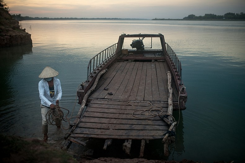 The driver of a ferry that shuttles locals between the village of Khpob Ateav and the island of Peam Reang docks his vessel as darkness approaches. Photo by Luc Forsyth.