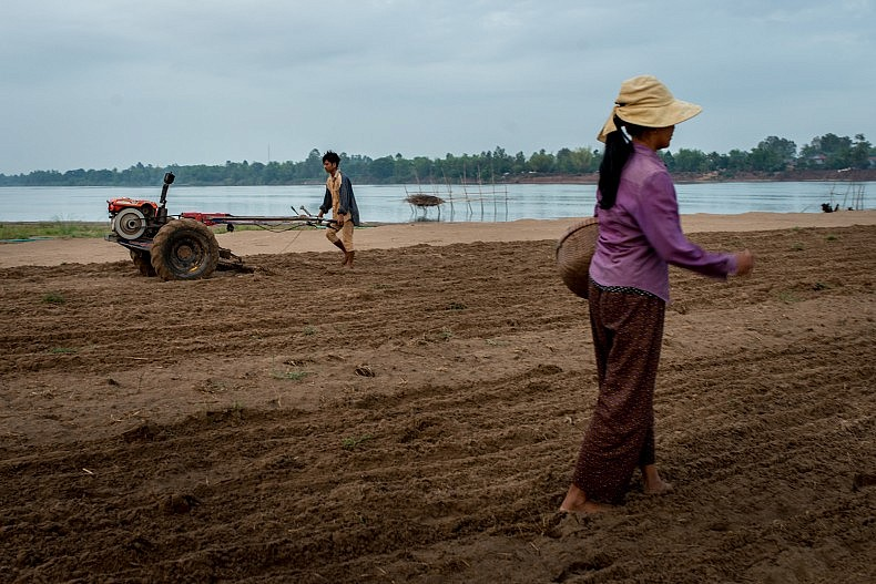 A mother and son work to cultivate a piece of sandy land on the coast of the island of Peam Reang. As erosion strips land from the banks of the Mekong, some of the sand washes up on the coast of the island, creating new farmland ideal for watermelon growing. Photos by Luc Forsyth.