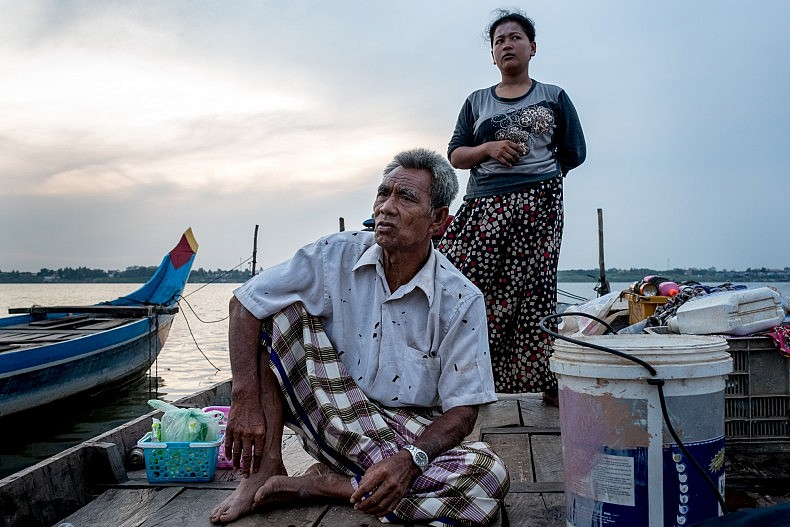 Mat Salas, 57, sits on his fishing boat as his daughter stands behind. Photo by Luc Forsyth.