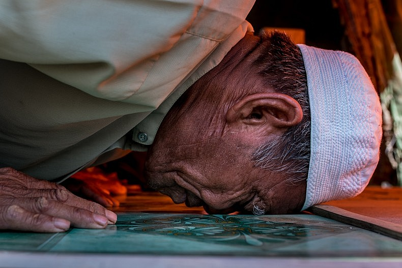 A Cham man touches his head to the floor in prayer. Photo by Luc Forsyth.