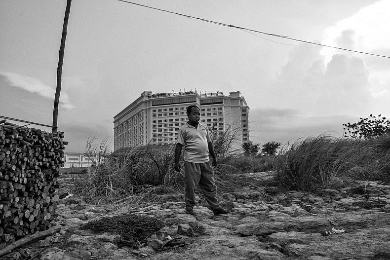 Yu Sos in stands in front of the newly erected Sokha Hotel. In Phnom Penh, a community of Chams live floating lives on boats and stilted houses, but the unprecedented pace of land development in Cambodia's capital puts them under constant threat of eviction. Photo by Gareth Bright.