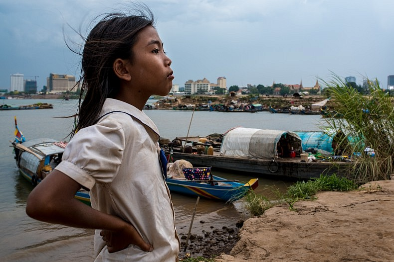 A Cham girl stands on the shoreline, overlooking the floating community where she lives. Photo by Luc Forsyth.