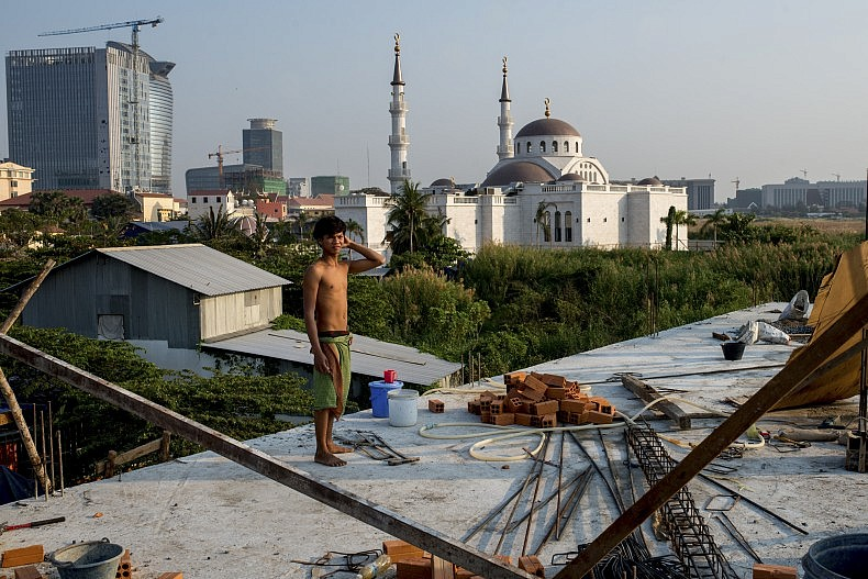 A construction worker stands on the roof of a building site on the outskirts of Phnom Penh's Boeung Kak Lake. Photo by Luc Forsytn.