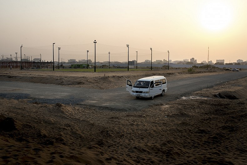 A van is parked in front of a series of football fields that have been built on the filled in remains of Phnom Penh's Boeung Kak Lake. The fields cost $10 per hour to play on, a prohibitively high price for many local residents. Photo by Luc Forsyth.
