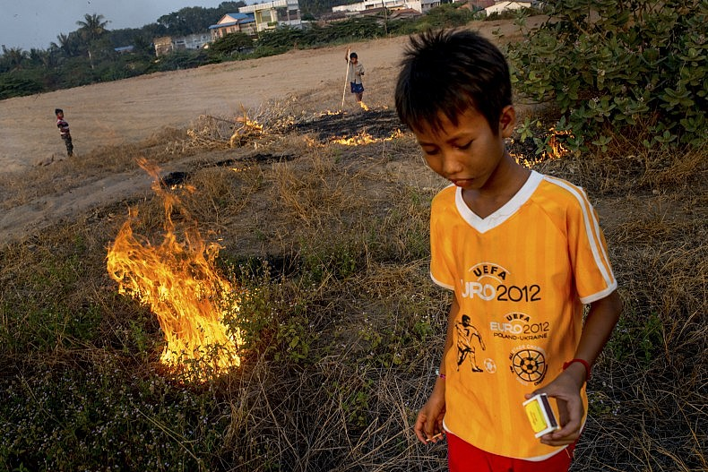Boys start small fires in the dry grass that has grown on the sand that was used to fill in Boeung Kak Lake, once Phnom Penh's largest freshwater lake. Photo by Luc Forsyth.