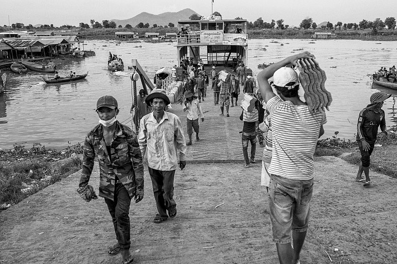 Workers carry ceramic tiles to a local ferry in the riverside city of Kampong Chhnang. Photo by Gareth Bright.