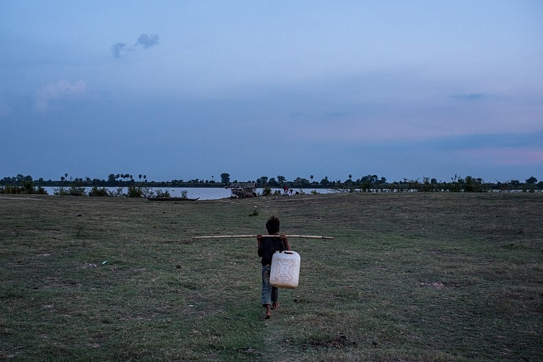A young boy walks towards the Mekong to collect water for his family in the remote community of Tae Pi. During the dry season the river level can recede up to a kilometer away from resident's homes. Photo by Luc Forsyth.