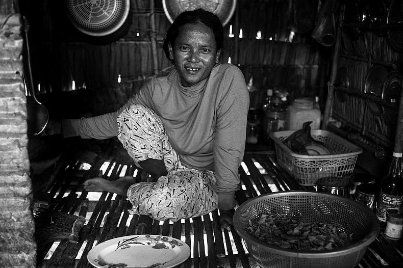 Jen Ta, a resident of the village of Tai Pi prepares an early morning breakfast of dried fish and rice for her family. Photo by Gareth Bright.