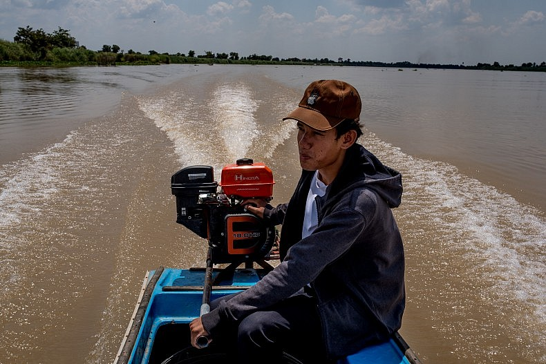 A teenager drives his boat between the city of Kampong Chhnang and the remote village of Tae Pi. Photo by Luc Forsyth.