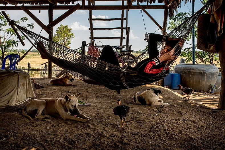 During the heat of the day, a teenager relaxes under the shade of his family home. Temperatures can approach 40 degrees Celsius (104 Fahrenheit) on a daily basis during the dry season. Photo by Luc Forsyth.