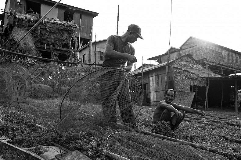 A soldier, who works part time as a fisherman to earn extra money, mends his nets in the riverside city of Kampong Chhnang. Photo by Gareth Bright.