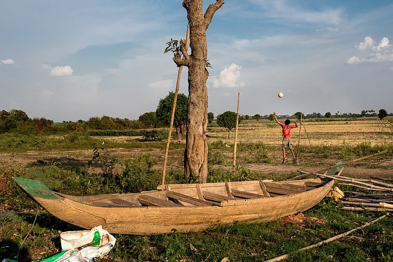 A teenage boy practices volleyball on a dry patch of ground in the remote village of Tae Pi. During the rainy season, these fields would be innundated by water. Photo by Luc Forsyth.