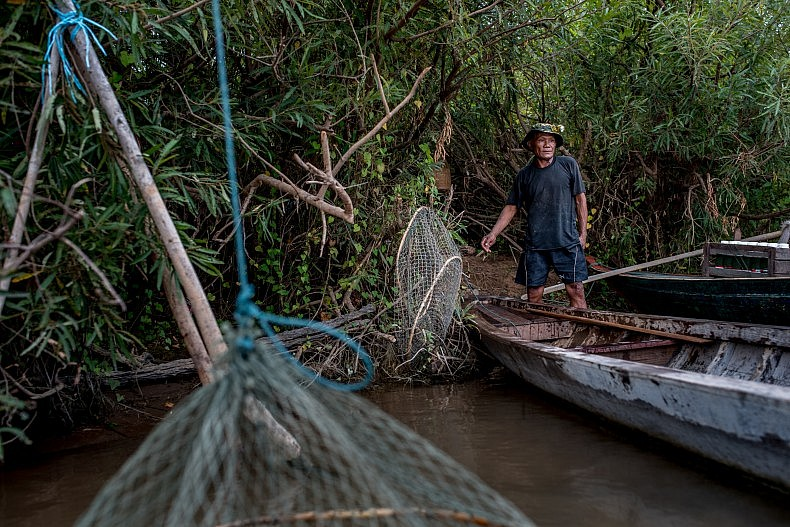 Thon Min, 65, hangs his fishing nets from trees along the banks of the Mekong river. When he catches enough fish, the surplus will be sold at a nearby market, while the remainder are kept alive until they are eaten. Photo by Luc Forsyth.
