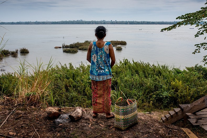 Kuch Hen, 45, looks out over the Mekong river. Her family supports itself entirely from the river, and will be heavily affected by the Chinese-owned Sesan II dam. Photo by Luc Forsyth.