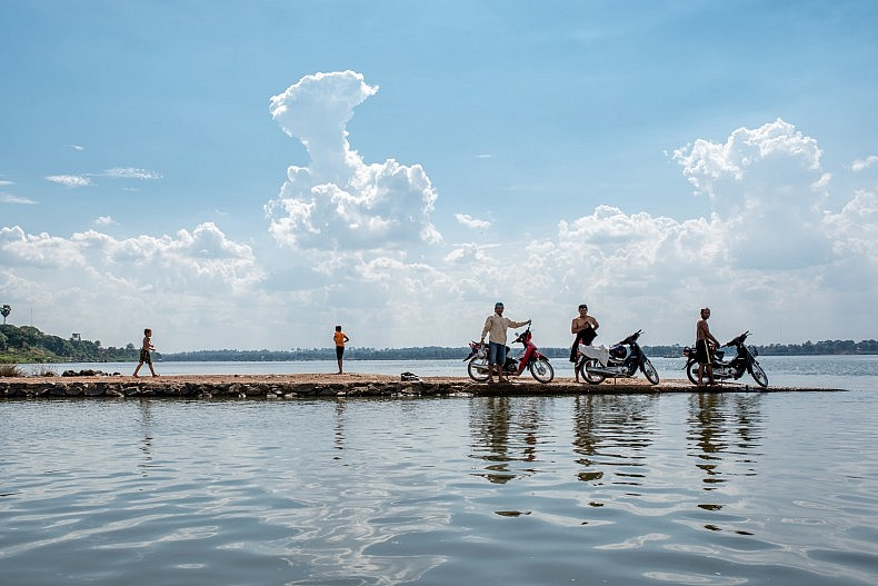 Locals gather along a pier extending into the Sekong River in the city of Steung Treng.  The Sekong is a major tributary of the Mekong and will be heavily affected by the Sesan II dam. Photo by Luc Forsyth.