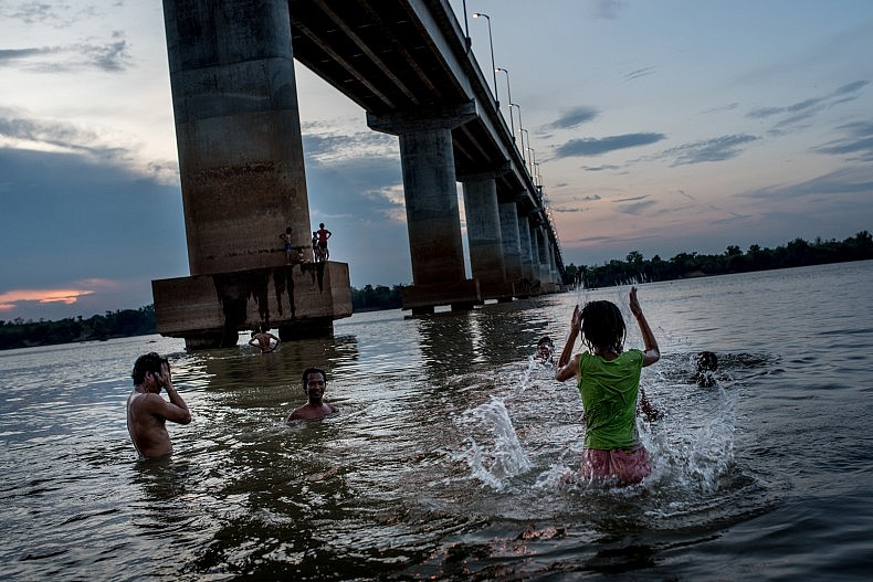 People play and relax in the water under the pilings of a bridge over the Sekong river in the city of Steung Treng. Photo by Luc Forsyth.