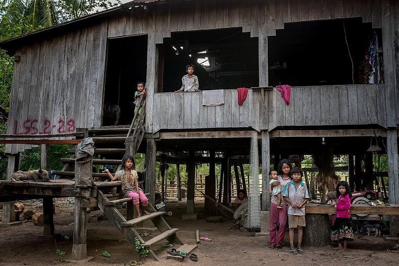 A Bunong family in front of their house in the village of Kbal Romeas. The red markings on their house indicate the family has agreed to the compensation package offered by Sino Hydro - the Chinese firm building the Sesan II dam - and will vacate their property. Photo by Luc Forsyth.